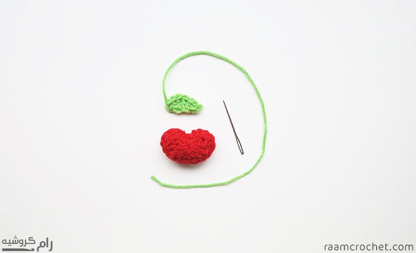 Use a needle to sew the leaf to the apple
